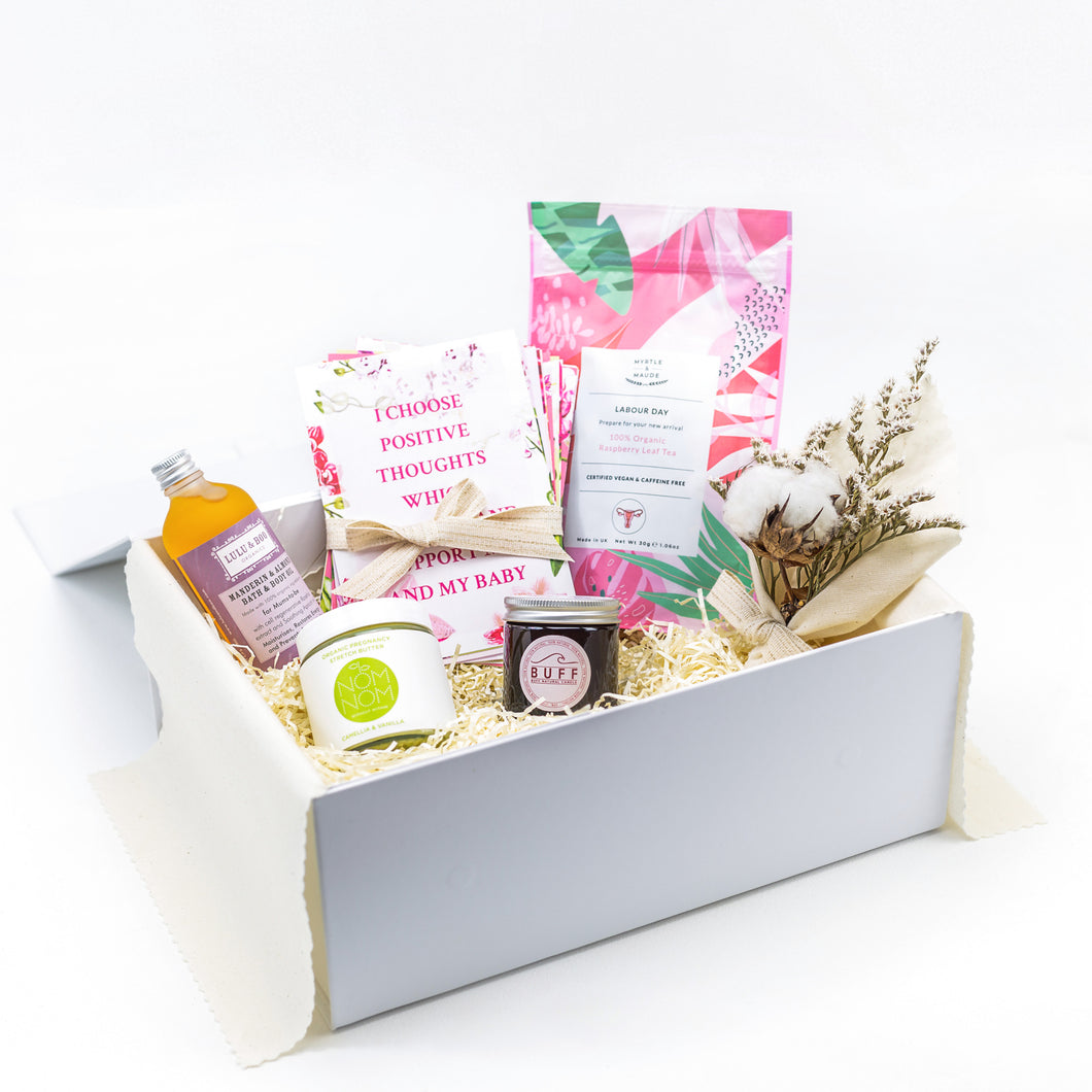 Amala Curations White Luxury Gift Box, lined with cream fabric, with 5 organic products (relaxing bath and body oil, stretch butter, affirmation cards, mama candle, raspberry leaf tea) and a cotton flower bouquet