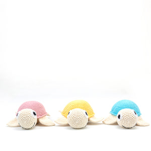 Amala Curations Luxury Gifts - 3 organic cotton crochet turtles, 1 in pink, 1 in yellow, 1 in blue; all lined up facing the camera.