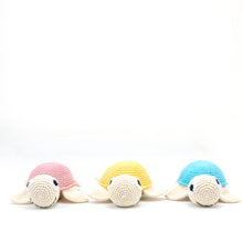 Load image into Gallery viewer, Amala Curations Luxury Gifts - 3 organic cotton crochet turtles, 1 in pink, 1 in yellow, 1 in blue; all lined up facing the camera.