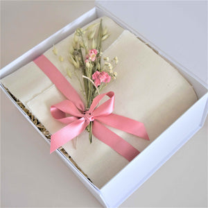Amala Curation's White Good Vibes Gift Box, wrapped with cotton fabric, pink recycled ribbon and decorated with pink and natural dried flowers