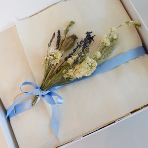 Amala Curation's Relax & Pamper Deluxe Gift Box Wrapped in cream colour cotton fabric, light blue recycled ribbon and blue and cream dried flowers