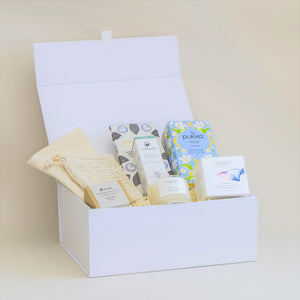 Amala Curation's Relax & Pamper White Gift Box with Acala Chamomile and Lavender Soap with Sisal Bag, Wildheart Organic Tranquil Travel Candle, Odylique Lemon Butter Hand Smoothie, Divine Organic Chocolate Bar and Pukka Relax Tea
