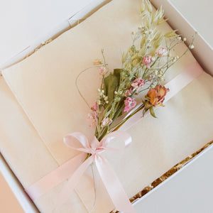 Amala Curation's Restore Deluxe Gift Box Wrapped in cream colour cotton fabric, light pink recycled ribbon and pink and cream dried flowers