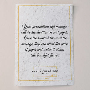 Piece of ivory coloured seed paper, with Amala Curation's logo and a note detailing that your personalised gift message will be written here