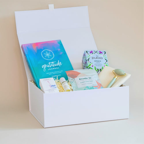 Amala Curation's Serenity Deluxe Gift Box with Wildheart Organic's Tranquil Aromatherapy roll on, Verdant Alchemy's Breathe In Bath Salts, Happi Empire Gratitude Journal, Jace Facial Roller, Pukka Peace Organic Tea