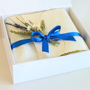 Amala Curation's Sleep Well Gift Box Wrapped in cream colour cotton fabric, blue recycled ribbon and blue and cream dried flowers