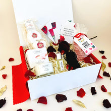 Load image into Gallery viewer, Amala Curations Valentine's Couple's Luxury, Ethical Gift Box with candle, couple's conversation cards, massage oil, dark chocolate hearts, organic bath bombs, in white gift box with red rose petals