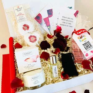 Amala Curations Valentine's Couple's Luxury, Ethical Gift Box with candle, couple's conversation cards, massage oil, dark chocolate hearts, organic bath bombs, in white gift box with red rose petals