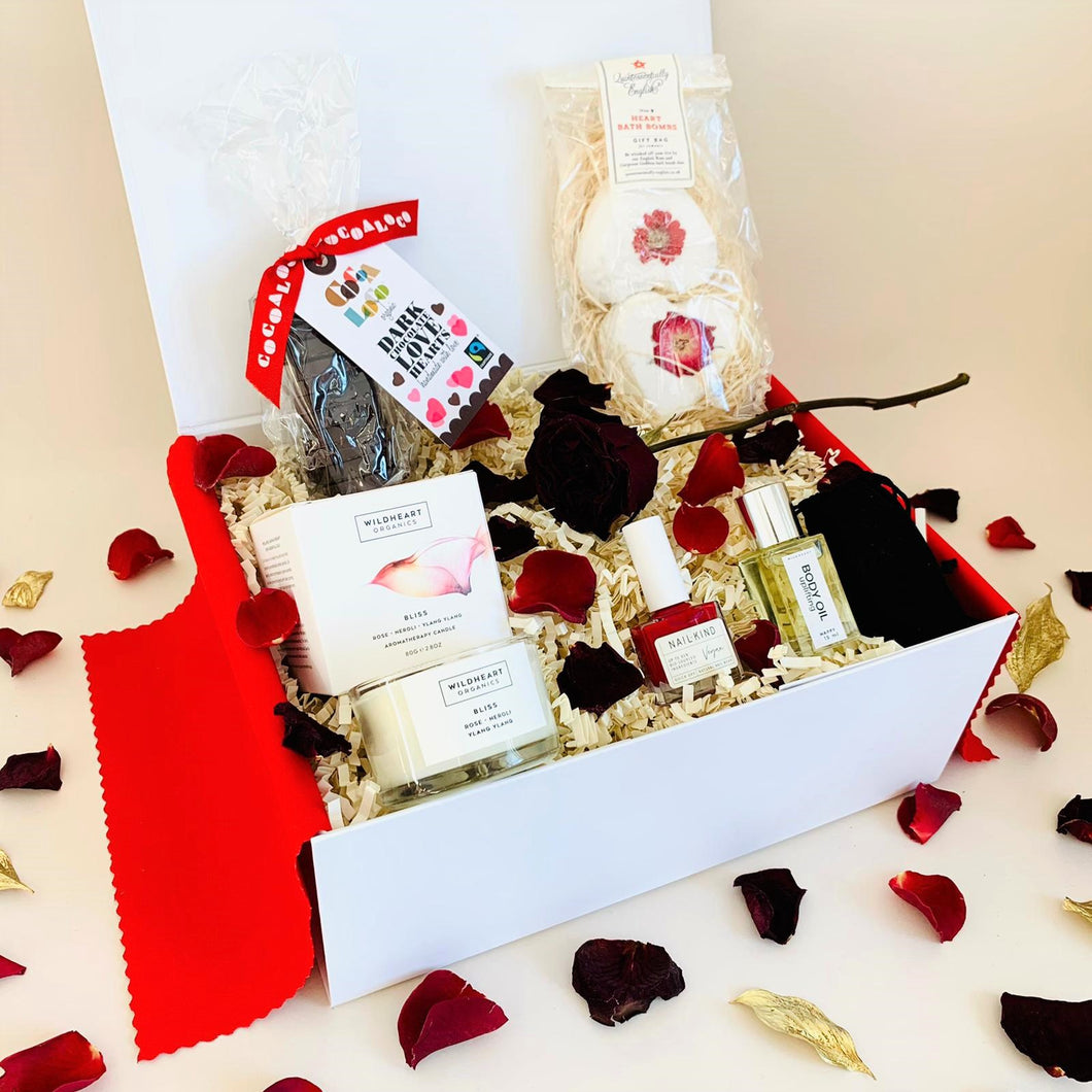 Amala Curations Valentine's Luxury, Ethical Gift Box with candle, red nail polish, massage oil, dark chocolate hearts, organic bath bombs, in white gift box with red rose petals