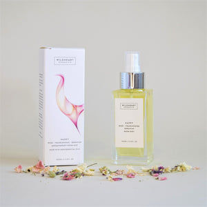 Wildheart Organic Happy Room Mist, White & Pink packaging, Glass Bottle, with dried florals scattered on surface