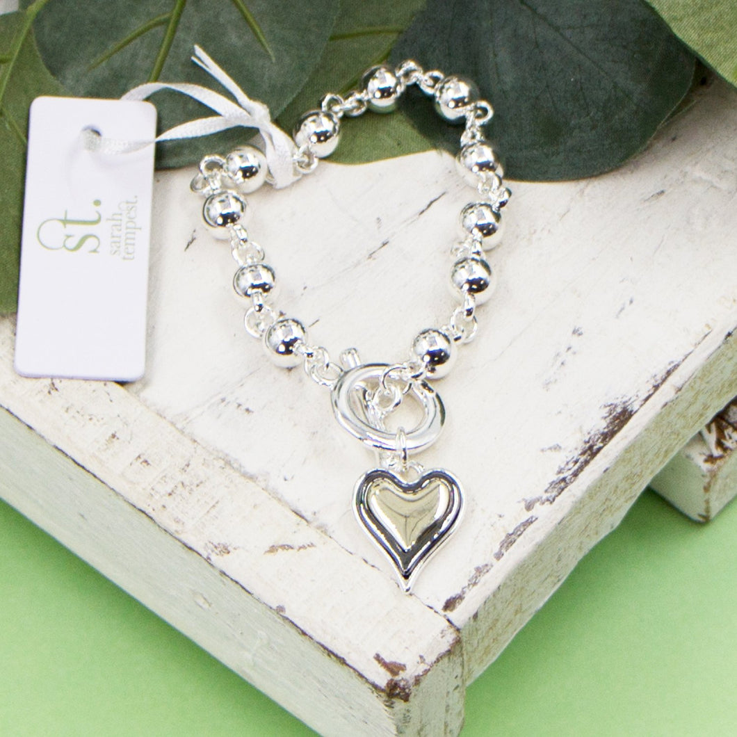 Multi tone heart charm beaded bracelet with t-bar clasp