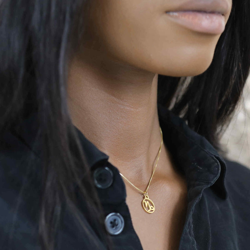 Model Wearing Charming Zodiac Capricorn Minimalist Solid Gold Pendant By Jewelry Lane