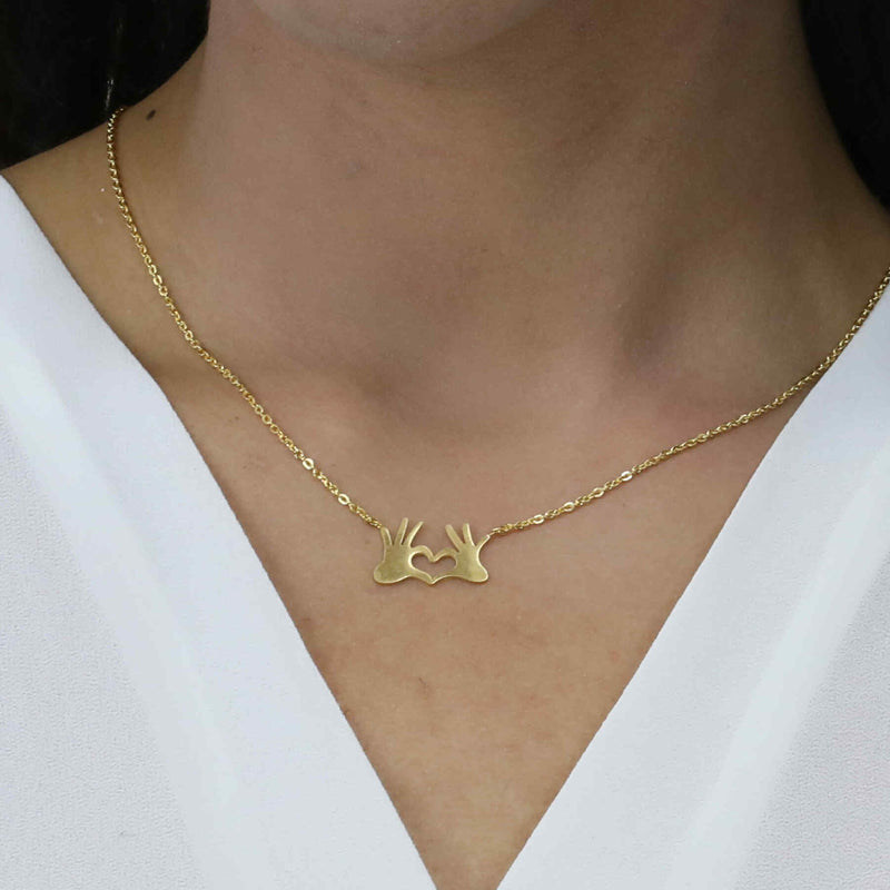Model Wearing Beautiful Modern Heart In Hand Solid Gold Necklace By Jewelry Lane