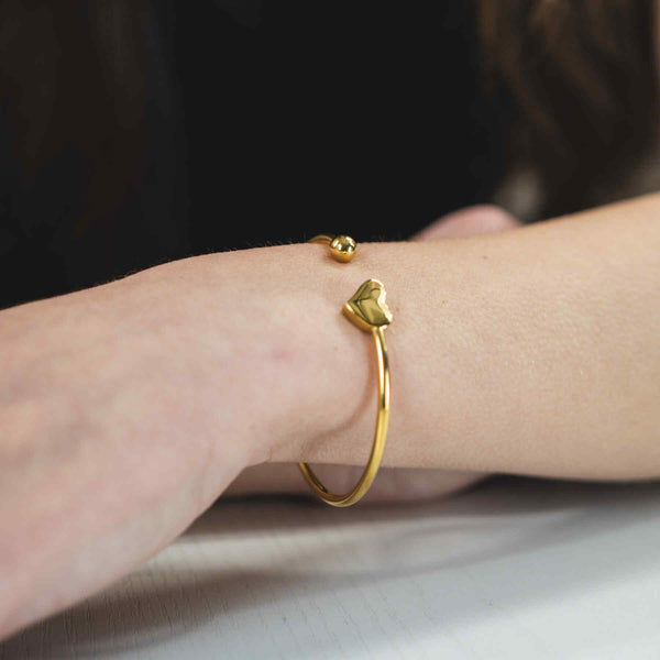 Model Wearing Beautiful Round Single Heart Solid Gold Cuff Bangle by Jewelry Lane