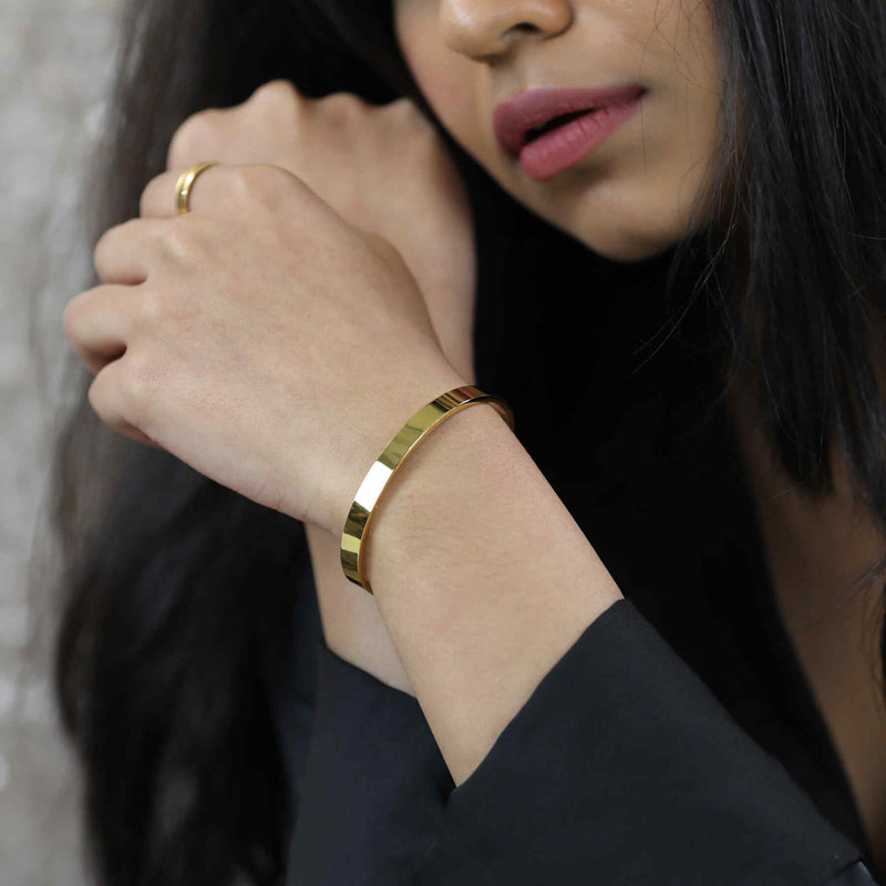 Model Wearing Smart And Chic Open Plain Cuff Solid Gold Bangle By Jewelry Lane