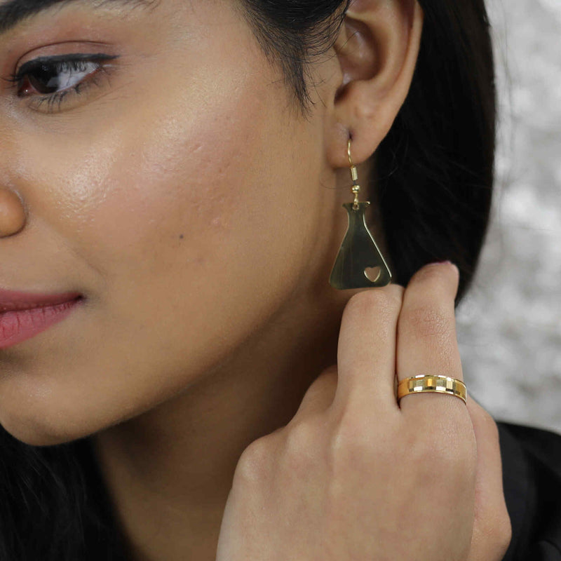 Model Wearing Beautiful Design Science Beaker Solid Gold Love Earrings By Jewelry Lane