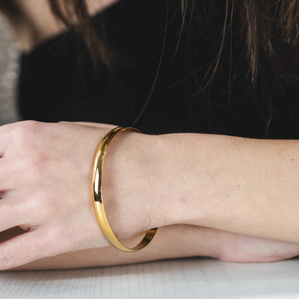 Model Wearing Beautiful Timeless Polished Solid Gold Bangle by Jewelry Lane