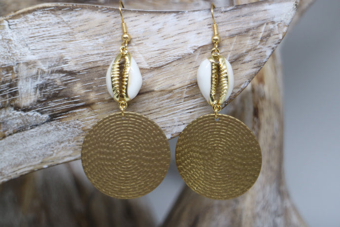 Gold trimmed cowrie shell earrings with raw brass charms