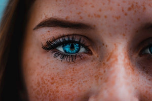 Woman with freckles and stunning aquamarine eyes.