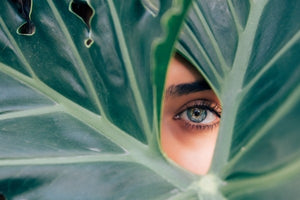 Woman with green eyes looking through a gap in a large deep-green leaf. The Toxic 10: Skincare ingredients to avoid. KPS Essentials Skincare.