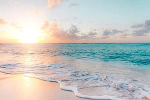 Sunrise over an aquamarine ocean and white sand beach.