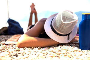 Woman with white hat laying on rocky beach. Sun protection.