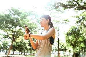 Woman checking cell phone and watch in running clothes outdoors.