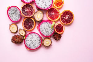 Pink background with antioxidant-rich rambutan, dragon fruit, and blood orange, all halved and set in a cluster.