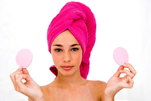 Young woman holding two cloth circles wrapped with a pink hair towel.