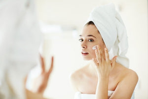 Woman with white towel on applying face cream.