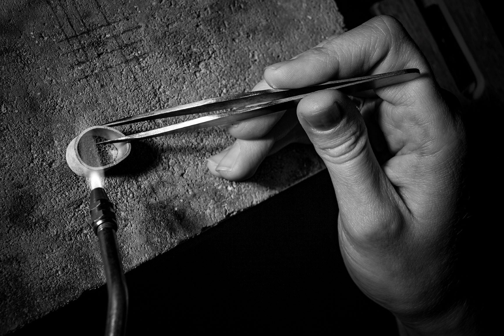 Jeweler at the bench soldering a ring