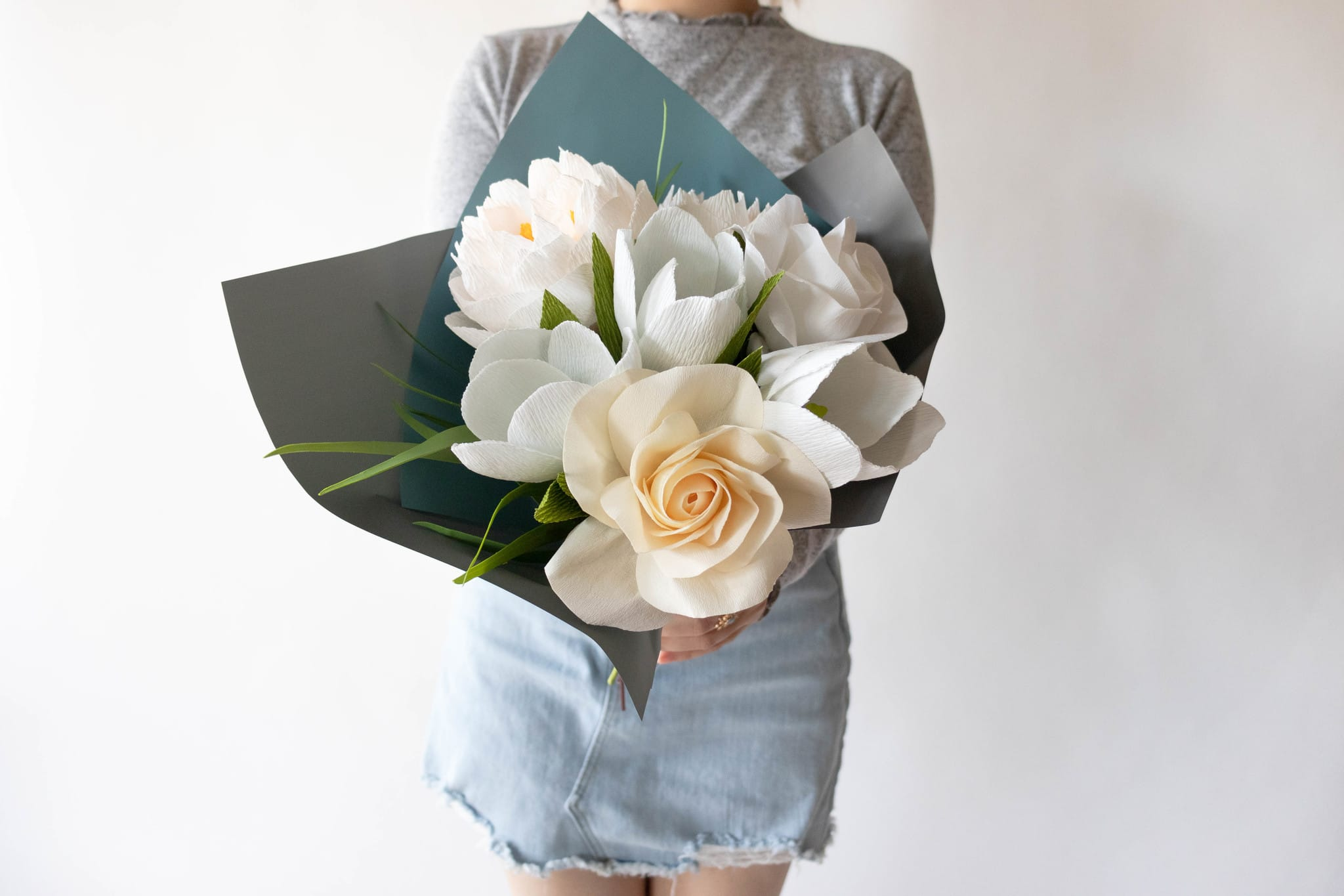 Florist holding a bouquet of paper flowers paired with faux greenery