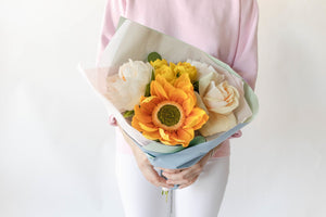 Florist holding a paper flower bouquet paired with preserved greenery