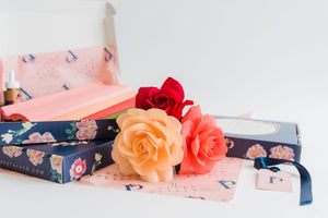 Paper roses next to a paper flower making kit containing European crepe paper and glue