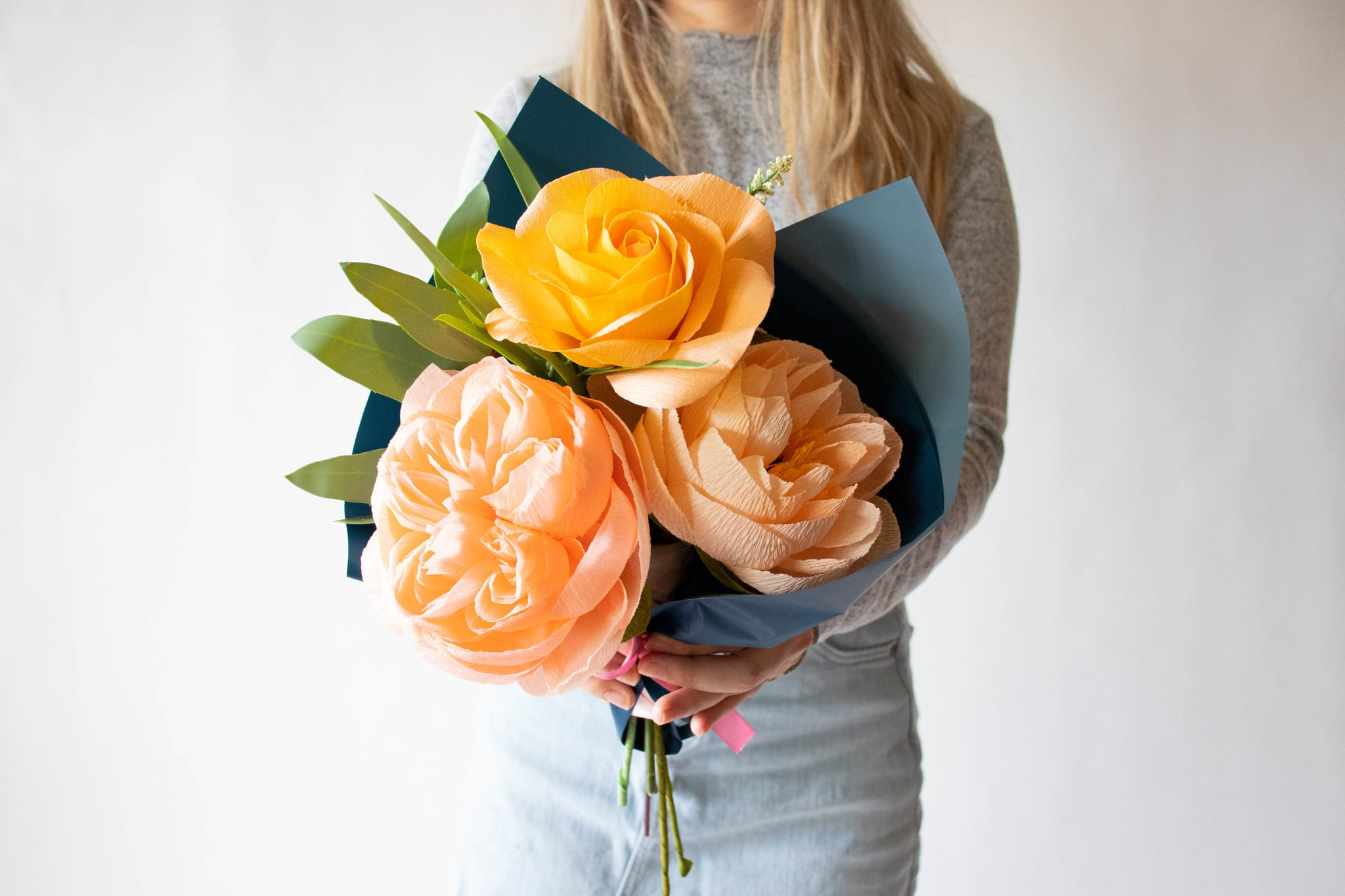Florist holding a colorful bouquet of paper flowers and faux greenery