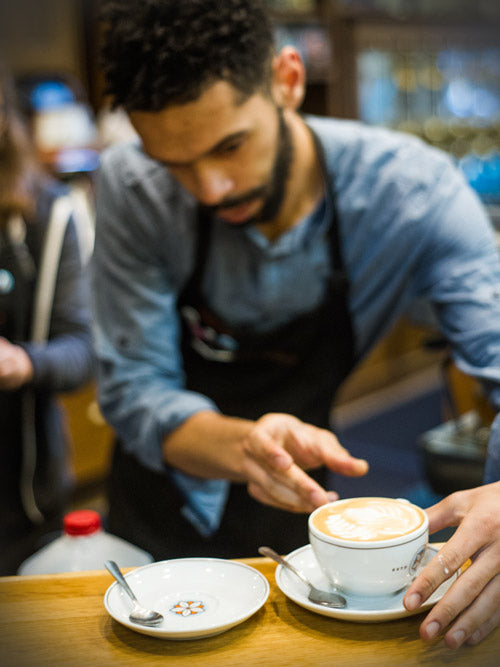 a barista places a beautifully poured latte onto a saucer