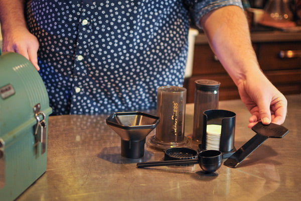an Aeropress on a countertop with all of its included components, scoop, funnel, filter holder, paper micro filters, and stirrer