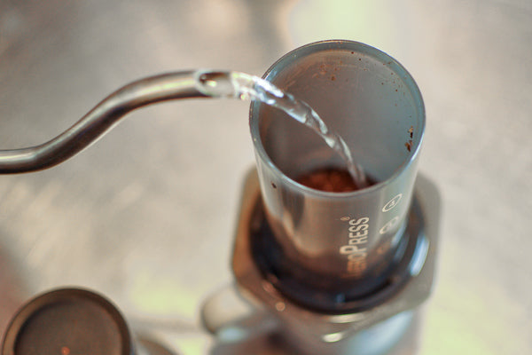 hot water is poured from a goose-neck kettle over the grounds in the AeroPress brewing chamber