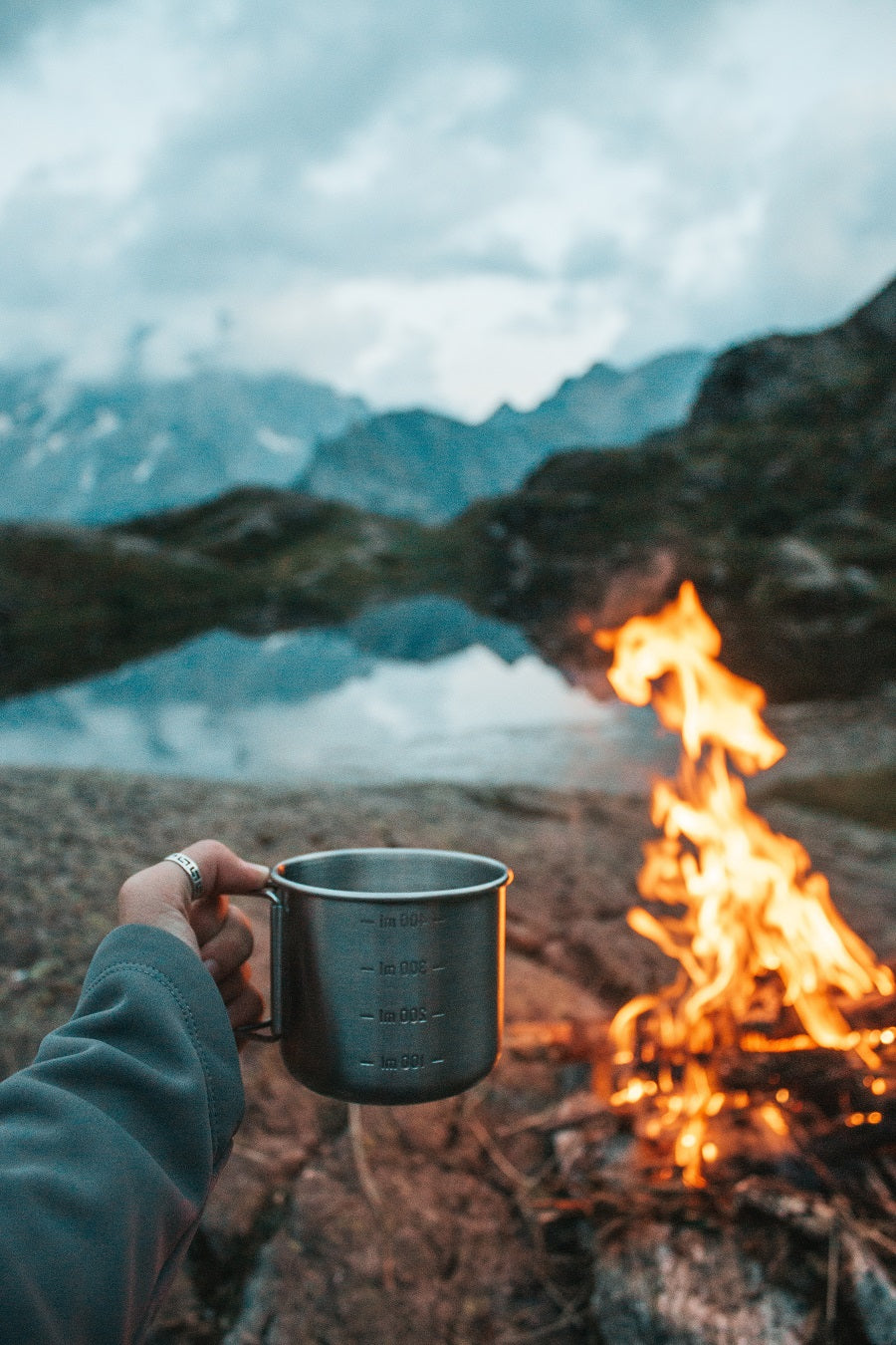 A hand holding a metal camping mug full of coffee while a campfire and mountain peaks fill the background