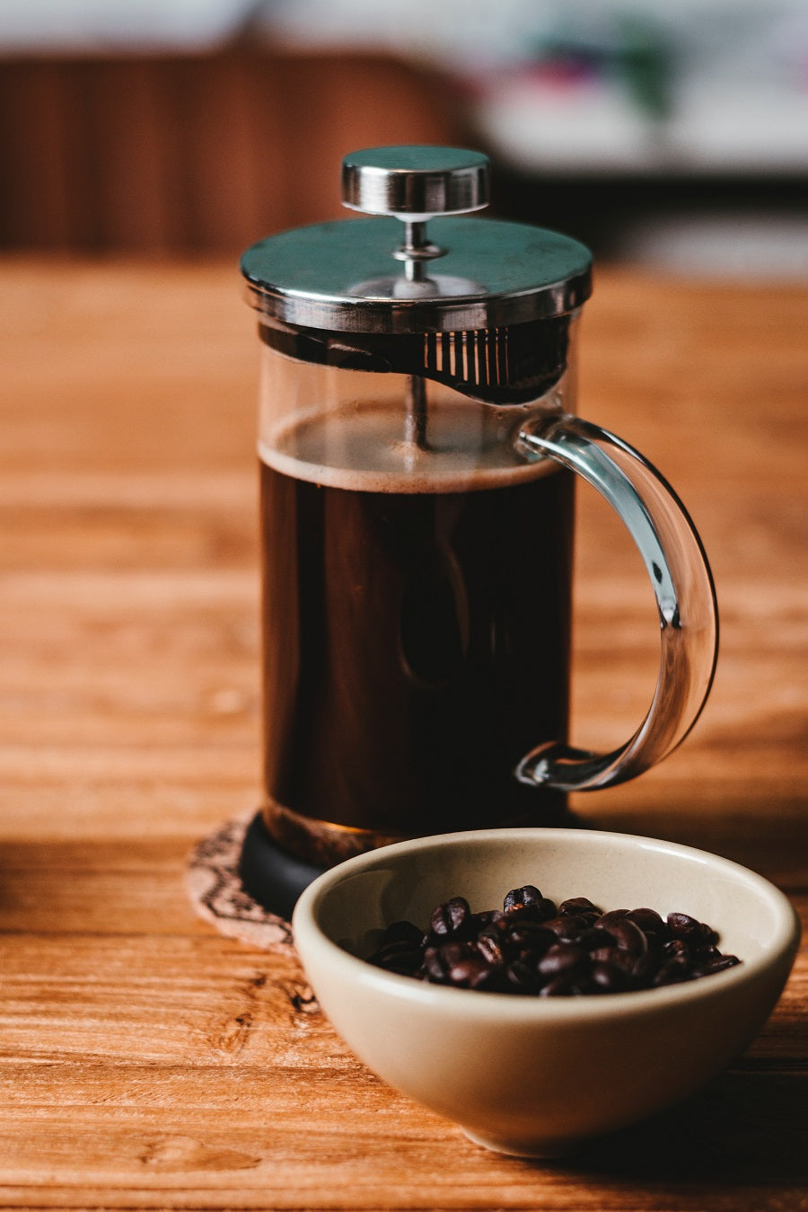 French Press next to white bowl with coffee beans in it