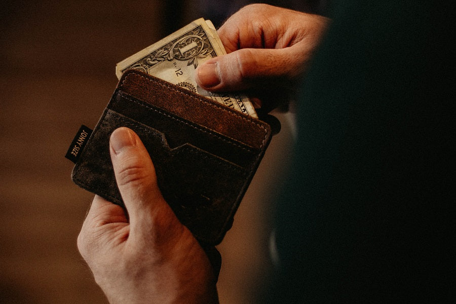 hand pulling money out of wallet
