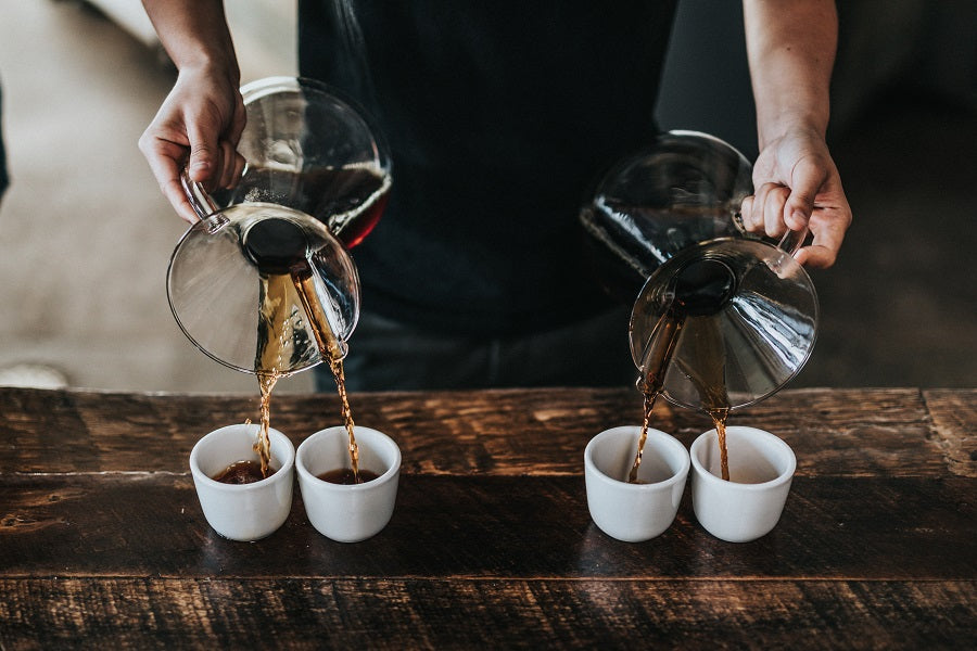 Two Chemexes pouring coffee into four cups