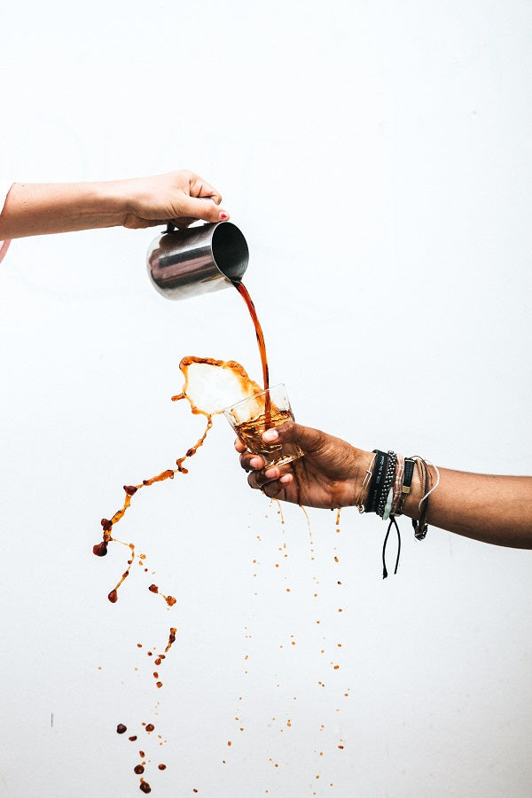 coffee pouring into a cup and spilling out