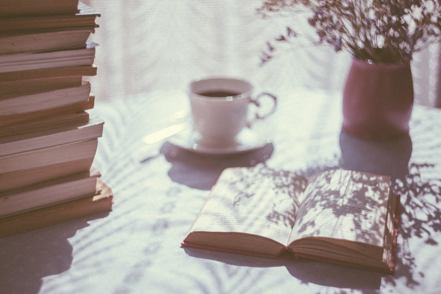 hazy morning light shining on a open book and a cup of coffee