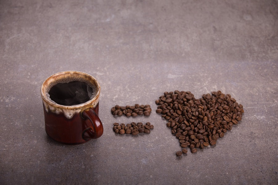 A cup of steaming coffee sits beside coffee beans which have been arranged into the shapes of an equals sign, and a heart