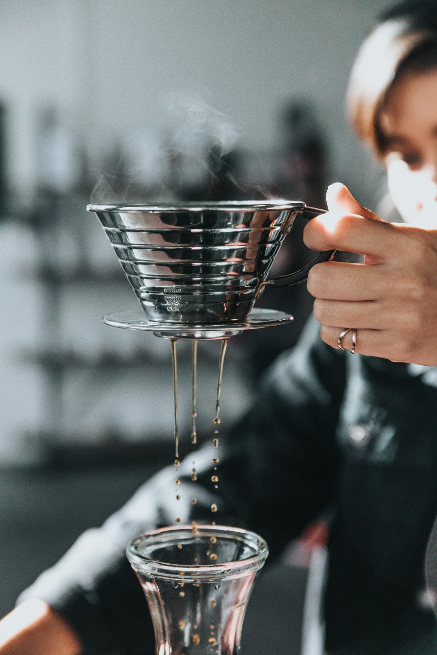 steam coming out of a stainless steel pour over that is brewing coffee into a glass carafe