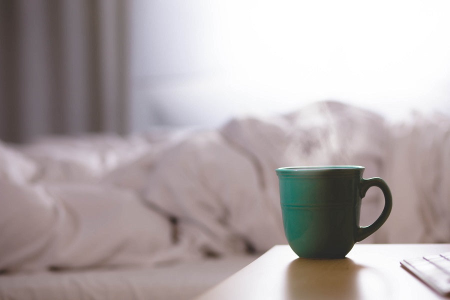 steaming blue mug on side table with white bedding in background