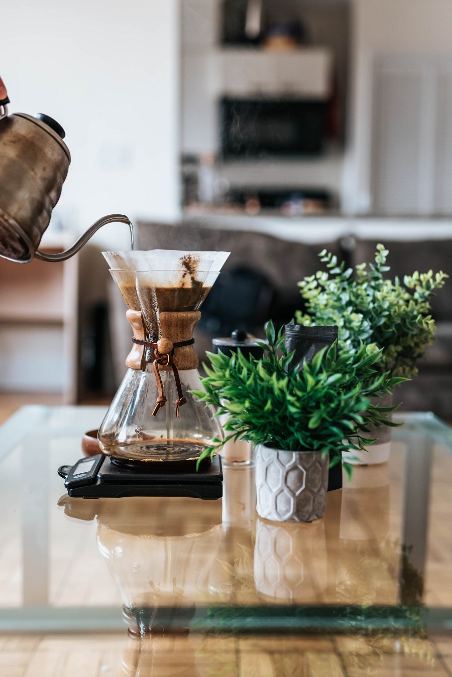 A Hand pours steaming water from a kettle into the top of a coffee loaded Chemex Pour Over brewer that sits on a modern glass coffee table