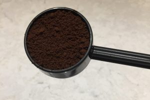 An AeroPress scoop filled with coffee