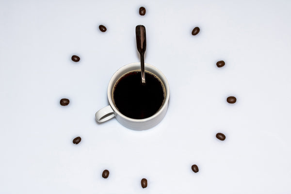 a clock made from a mug for the center and coffee scoops as the hands